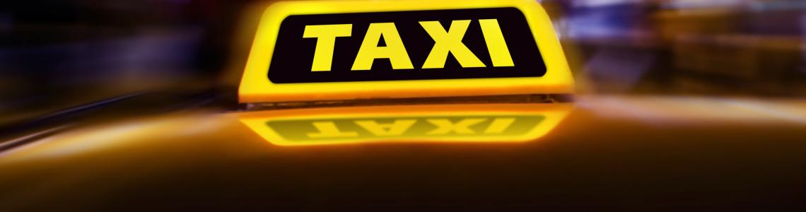 Taxi_sign_on_the_roof_of_car_on_the_street_at_night