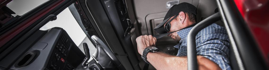 truck driver putting seat belt on