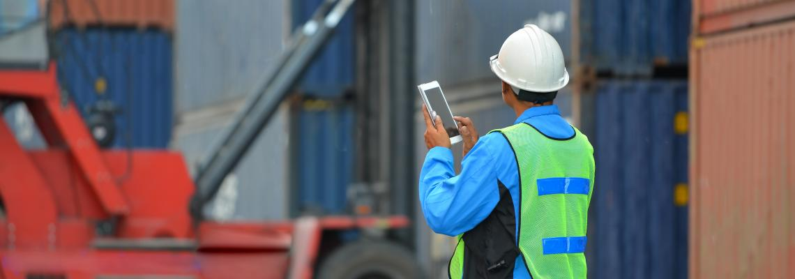 man with tablet and shipping containers