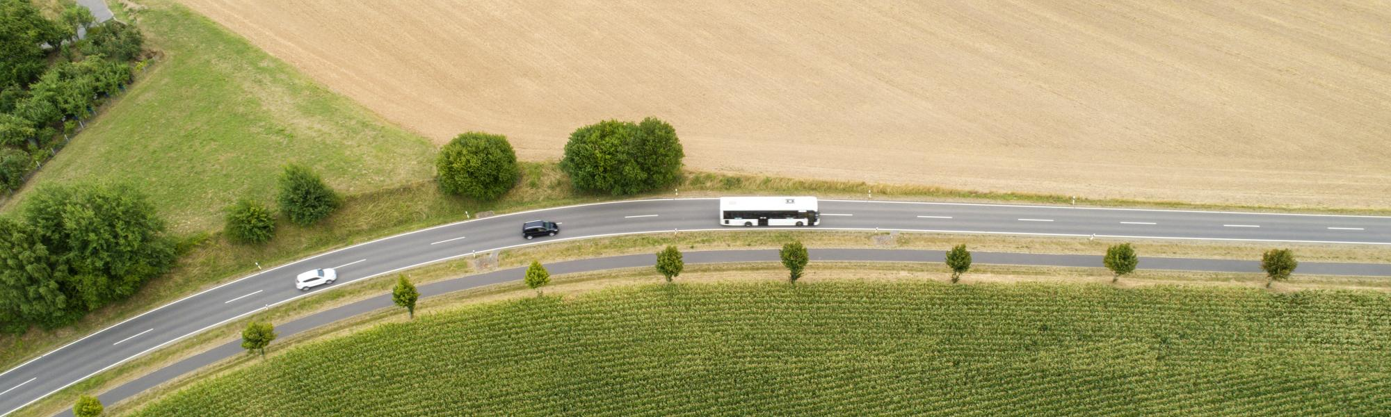 aerial view of a white coach driving on the road