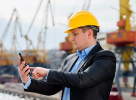 man checking smart phone wearing hard hat