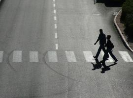 two people crossing the road zebra crossing
