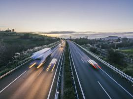 vehicles speeding along highway at dusk