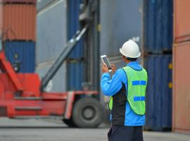 man with tablet shipping containers